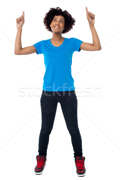 Amused young lady pointing and looking upwards Stock photo © stockyimages