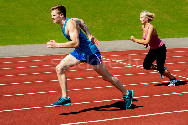 Athletes running on race track Stock photo © stockyimages
