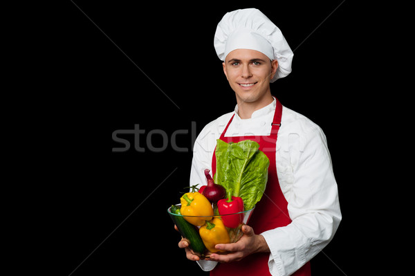 Handsome chef holding vegetables bowl Stock photo © stockyimages