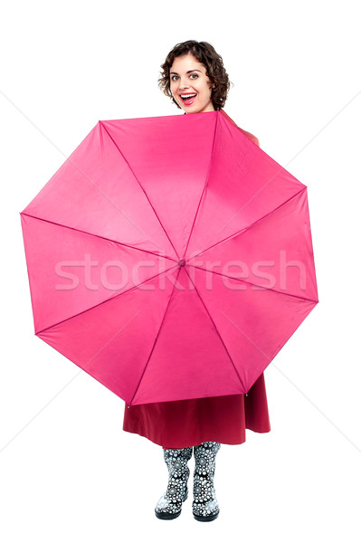 Cheerful woman being playful with umbrella Stock photo © stockyimages