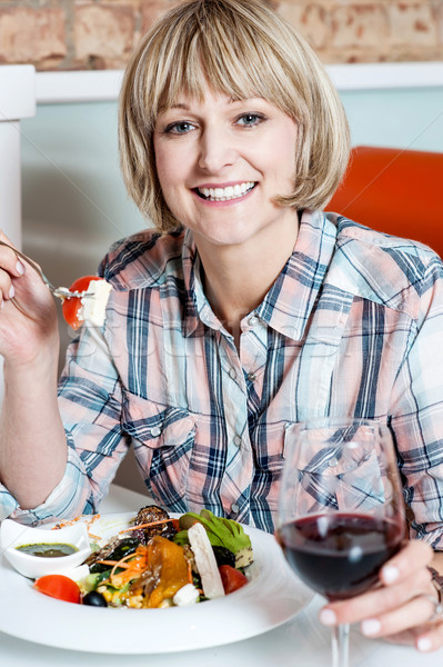 Woman relishing her meal with red wine Stock photo © stockyimages
