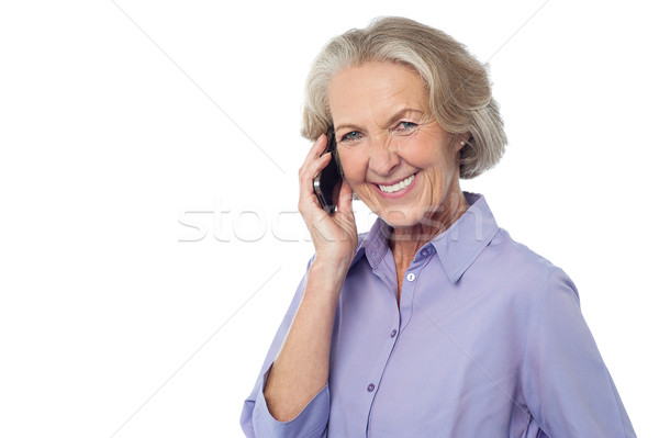 Senior smiling lady attending phone call Stock photo © stockyimages