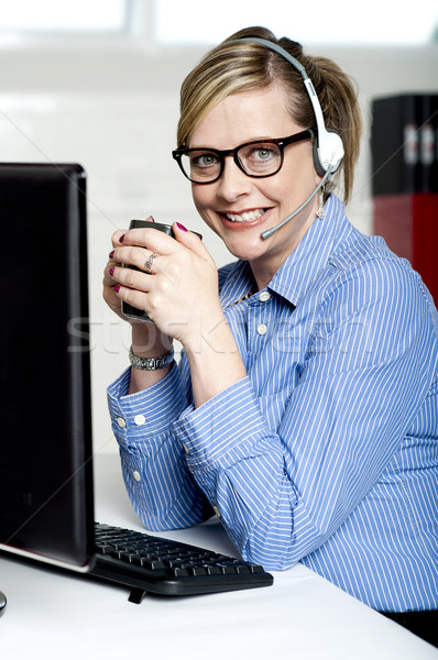 Stock photo: Help desk executive drinking coffee at work