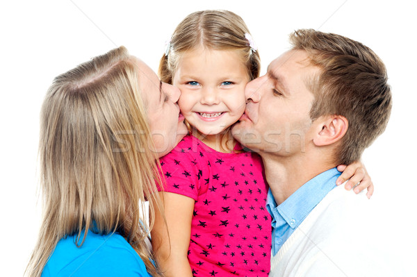 Mom and dad kissing their beautiful kid Stock photo © stockyimages
