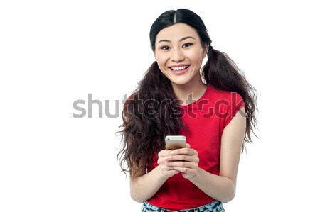 Pretty chinese girl reading funny message Stock photo © stockyimages