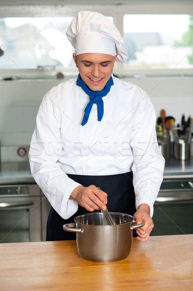 Young male chef with whisk and mixing bowl Stock photo © stockyimages