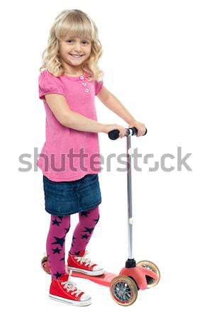 Happy little girl riding her scooter Stock photo © stockyimages