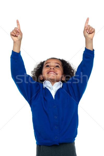 Amazed young school girl indicating upwards Stock photo © stockyimages