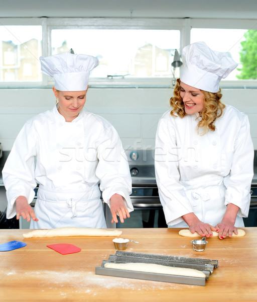 Senior chef teaching newbie female chef Stock photo © stockyimages