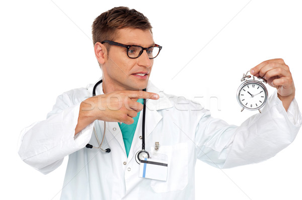 Shocking young doctor pointing at alarm clock Stock photo © stockyimages