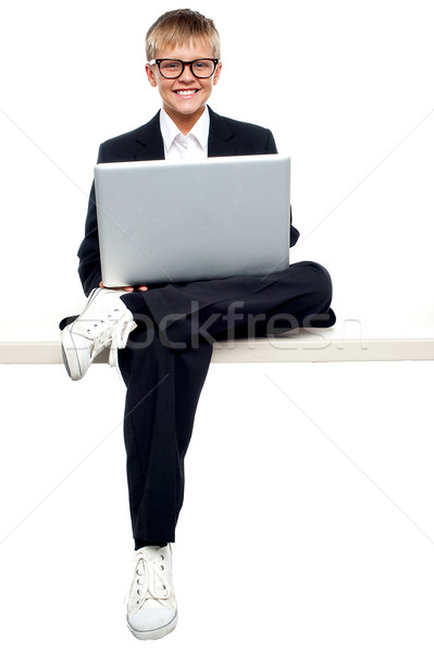 Smartly dressed young kid working on a laptop Stock photo © stockyimages