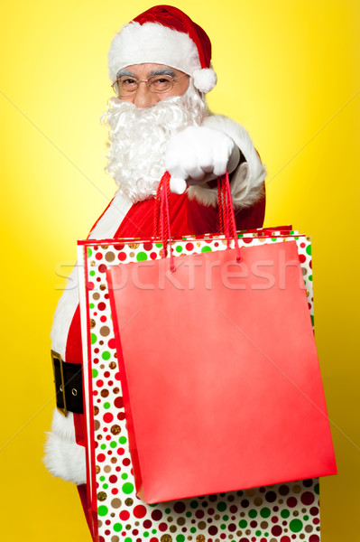 Cheerful Santa holding vibrant colored shopping bags Stock photo © stockyimages