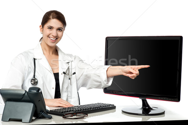 Female physician pointing at computer screen Stock photo © stockyimages