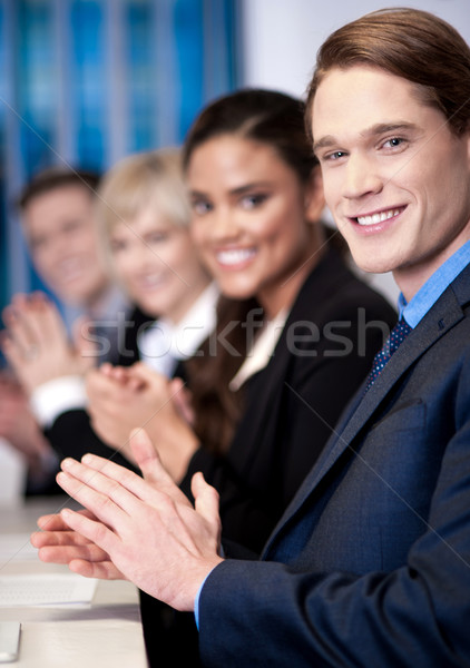 Corporate team sitting in a row and applauding Stock photo © stockyimages