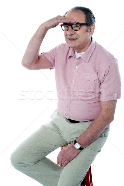 Seated handsome old man looking far away by Stock photo © stockyimages
