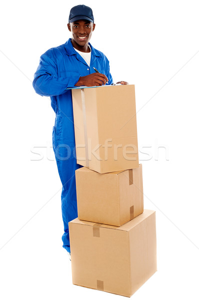 Cheerful delivery guy preparing receiving notice Stock photo © stockyimages