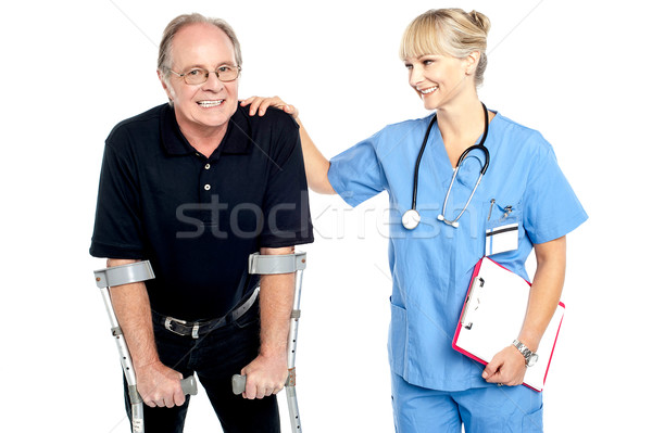 Cheerful doctor encouraging her patient to walk with crutches Stock photo © stockyimages