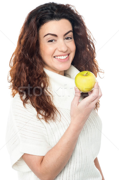 Joyous woman with an apple in hand Stock photo © stockyimages