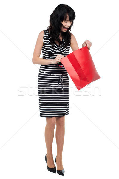 Young woman searching for her gift inside bag Stock photo © stockyimages