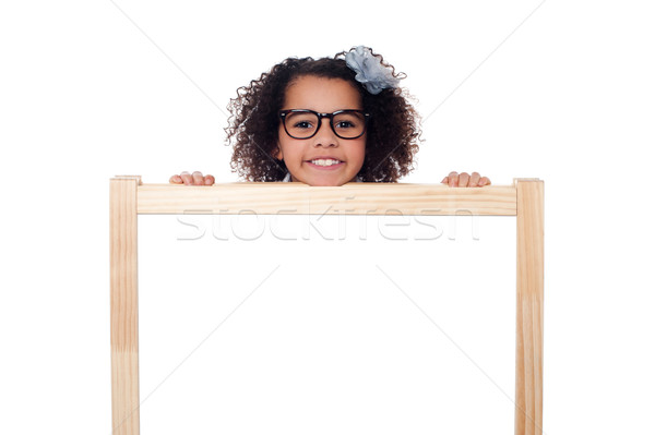 Girl peeping from behind white writing board Stock photo © stockyimages