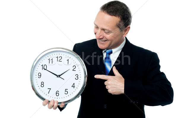 Smiling man holding a clock in his hands Stock photo © stockyimages