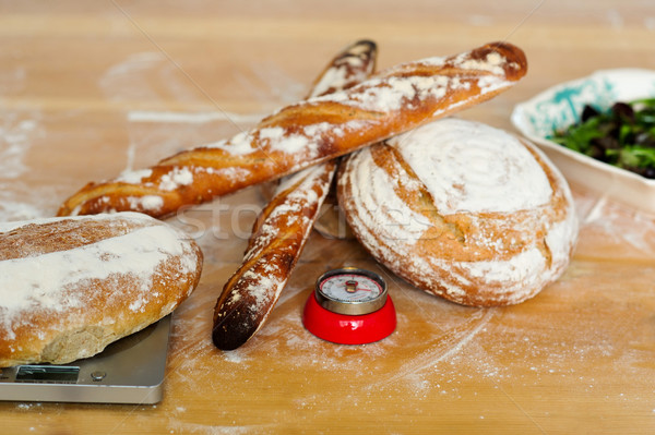 Baguettes and breads on wooden table Stock photo © stockyimages
