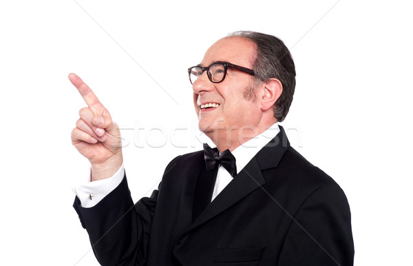 Aged man looking and indicating upwards Stock photo © stockyimages
