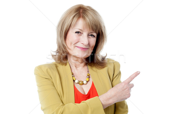 Smiling old lady pointing away Stock photo © stockyimages
