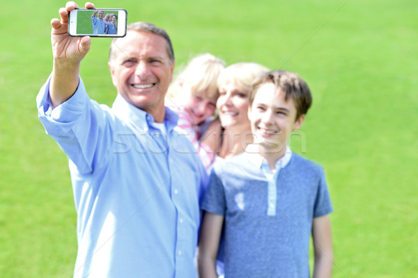 Father clicking family selfie, outdoors. Stock photo © stockyimages