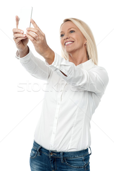 Pretty woman taking selfies with her smart phone Stock photo © stockyimages