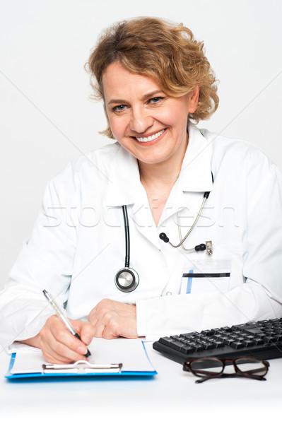 Szczęśliwy kobiet lekarz pracy biurko piśmie Zdjęcia stock © stockyimages