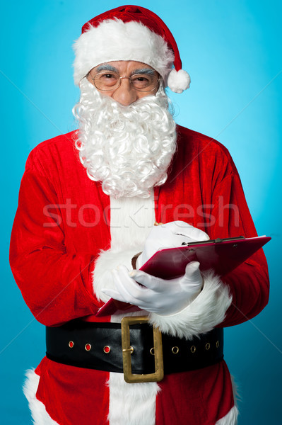 Father Nicholas preparing a list of gift recipients Stock photo © stockyimages