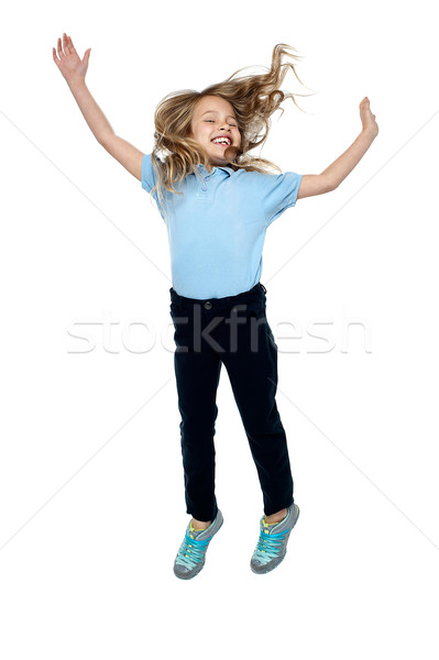 Delighted young girl jumping high in the air Stock photo © stockyimages