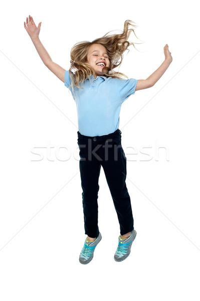Elragadtatott fiatal lány ugrik magas levegő fiatal Stock fotó © stockyimages