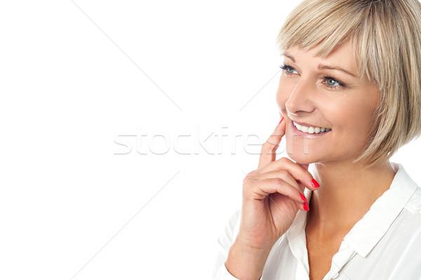 Smiling woman imagining something Stock photo © stockyimages