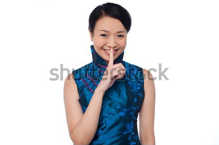 Fashionable woman putting a finger on her lips Stock photo © stockyimages