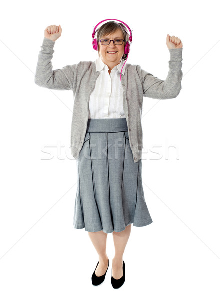 Cheerful aged woman enjoying music Stock photo © stockyimages