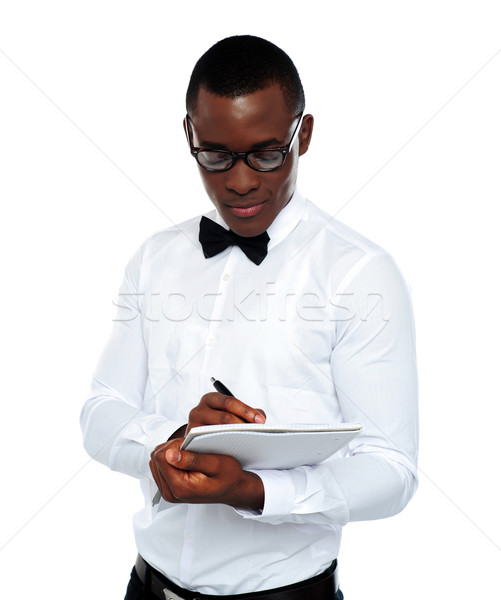 Confident young man writing on notepad Stock photo © stockyimages