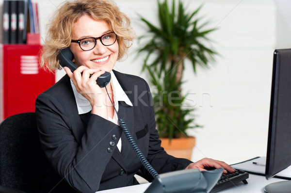 Front desk lady attending clients call Stock photo © stockyimages