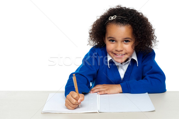 Cute primary kid writing her assignment Stock photo © stockyimages