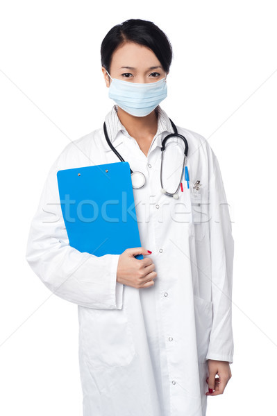 Surgeon holding clipboard. Face covered with surgical mask Stock photo © stockyimages