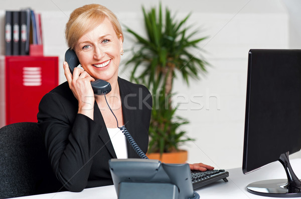 Secretary talking on phone with client Stock photo © stockyimages
