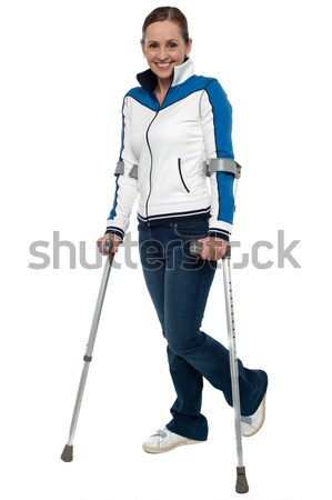 Woman walking with the support of crutches Stock photo © stockyimages