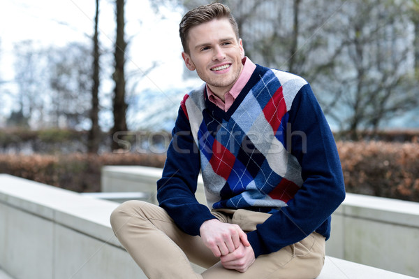 Stylish young man sitting in sidewalk Stock photo © stockyimages