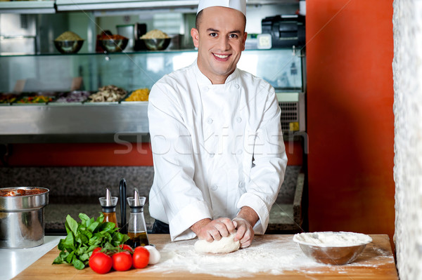 Smiling chef preparing pizza base Stock photo © stockyimages