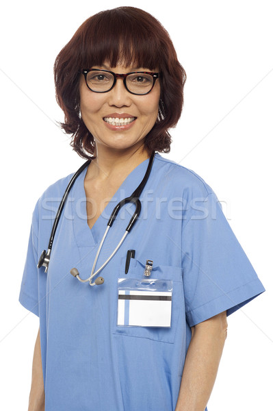 Pleasing female gynecologist posing with stethoscope Stock photo © stockyimages