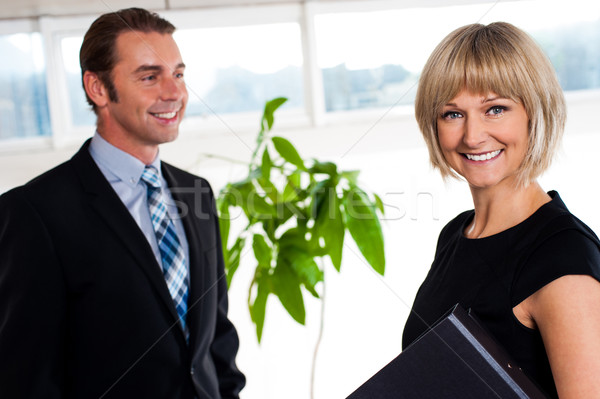 Handsome boss passing by smiling female colleague Stock photo © stockyimages