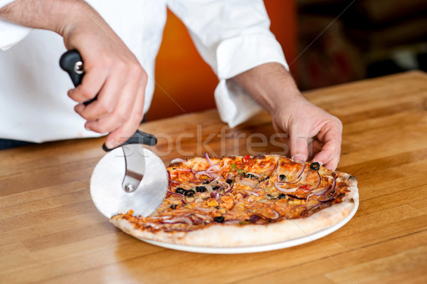 Chef cutting pizza with cutter Stock photo © stockyimages
