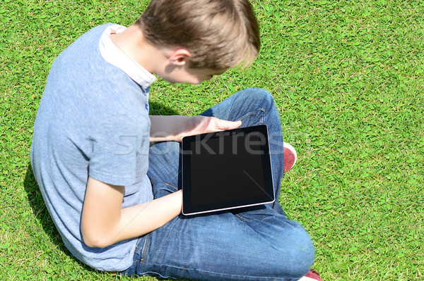 Boy relaxing in lawn and using tablet pc Stock photo © stockyimages