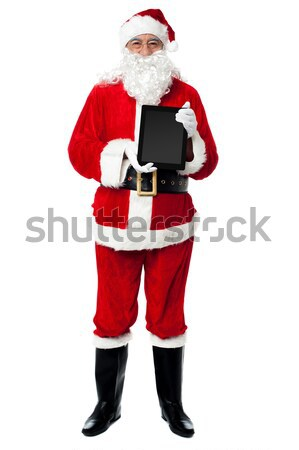 Saint Nicholas displaying a brand new tablet device Stock photo © stockyimages